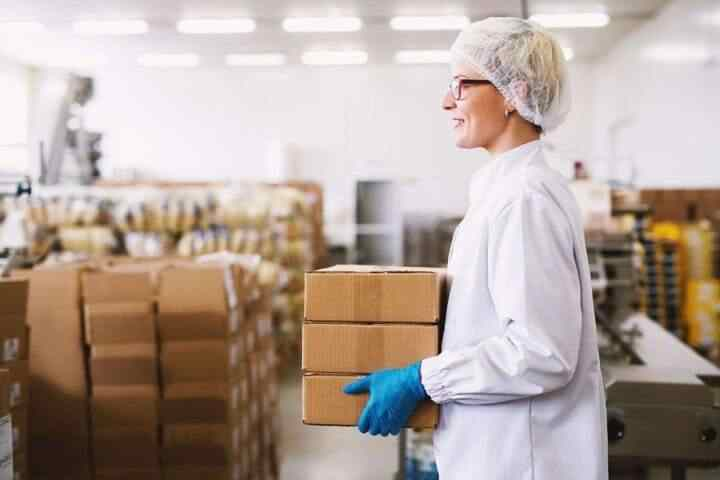 Young beautiful cheerful female worker is carrying a stack of boxes to cargo room.